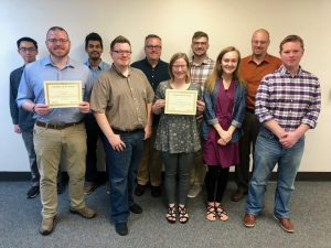 NETC members standing with team award